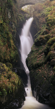 Aira Force waterfall emerging through a bridge, and falling in a torrent of white foam between moss covered rocks