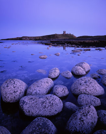View of Dunstanburgh Castle from the north west taken in the dusk twilight and showing the incoming tide
