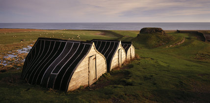 View of up-turned boats that have been converted into huts at Lindisfarne Castle