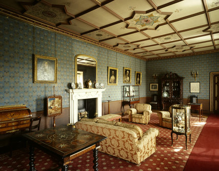 View of the Old Drawing Room at Oxburgh Hall showing the 18th century fireplace and Crace's heraldic ceiling painted after 1870