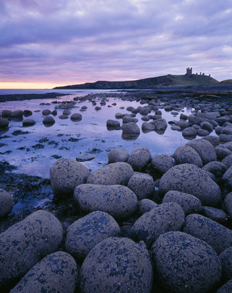View of Dunstanburgh Castle from the north west taken at dawn in the March (Spring) Equinox