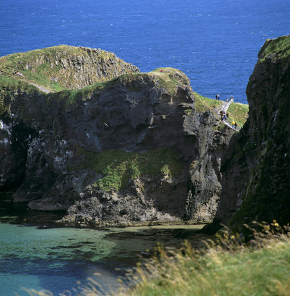 A view of Giant's Causeway, showing visitors crossing Carrick-A-Rede in the distance