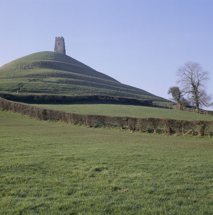 A view across a field to Glastonbury Tor with the remains of the 15th century tower at the summit