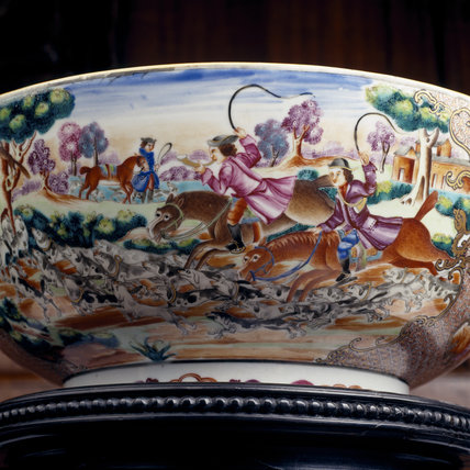 A close up of the outside of a porcelain bowl depicting a hunting scene with horse-back riders and beagles