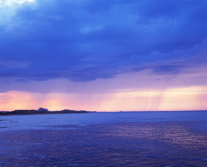A spectacular picture of the coast at Seahouses, the land silhouetted against an angry sky, with rain falling in the distance