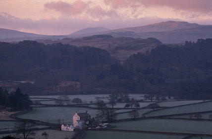 Eskdale near Boot at Dawn, a green landscape of fields with buildings in the distance