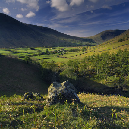 A view of sunlit fields, enclosed by stone walls,at Wasdale Head
