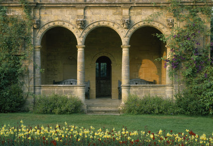The Italian loggia, built in 1920s, covered with Clematis jackmanii 'Superba' and roses in the Sunk Garden at Nymans