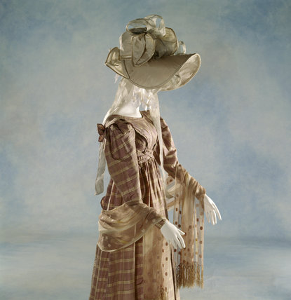 View of a c.1827-28 lilac silk taffeta dress with a white silk hat & shawl.