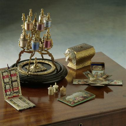 Close-up angled view of a group of needlework tools from Kay Shuttleworth Collection, Gawthorpe Hall on mahogany table