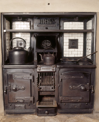Trident kitchen range installed in the still-room at Dunham Massey, supplied by Clement Jeakes during the modernisation of 1906, shows two kettles and a frying pan above two ovens