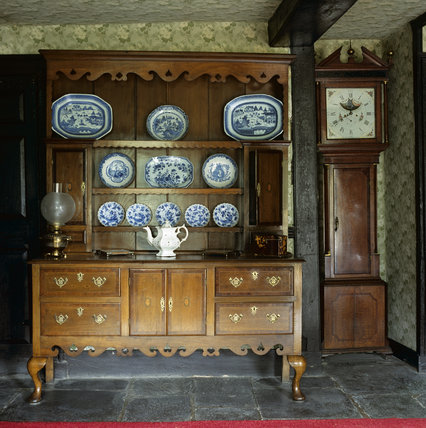 A local carved oak press cupboard at Hill Top, bought by Beatrix at a local farm sale, above which hang eight plates painted with animals and birds by her father, Rupert.
