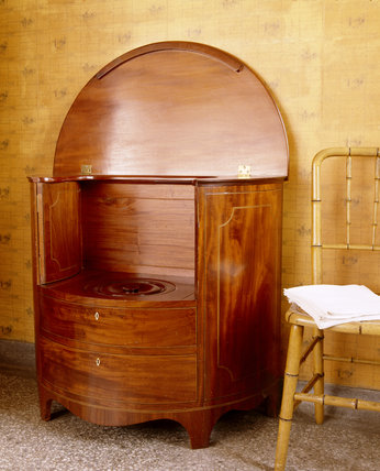 An elaborate commode in a wooden cabinet, with simulated cup- boards and drawers outlined in marquetry, in a bathroom at Dunham Massey,the oval lid is open showing an inner lid