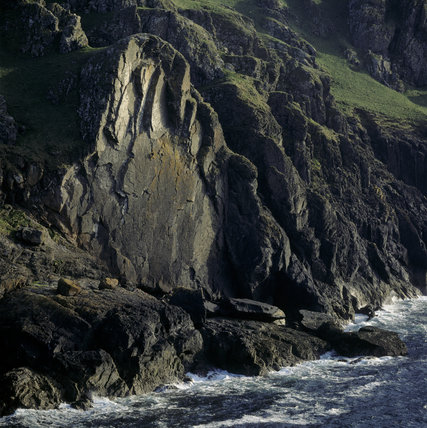 A vertical slab of rock below the Pentire/Rumps Walk within the six miles of N.T. property between New Polzeath & Port Quin. A rock climber can be seen about two-thirds of the way up.