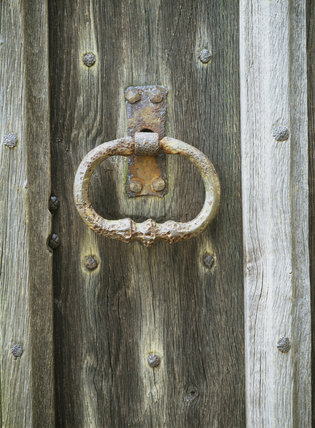Detail of a rusting door handle at Nymans Garden, taken on November, on a wooden door