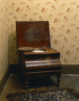 A wooden commode in a 1930s-style bedroom of the Birmingham Back to Backs