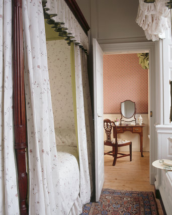 View of Anne Wordsworth's Bedroom showing the side of her four poster bed and through a door to her closet beyond at Wordsworth House
