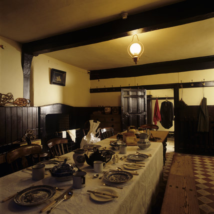 The interior of the Servants Hall at Speke Hall with the table laid out as it would have been in older times