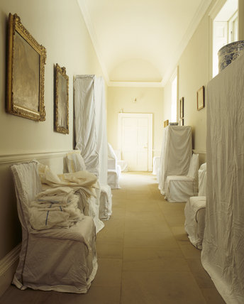 Dust sheets cover the furniture in the stone corridor for Cover furniture with sheets