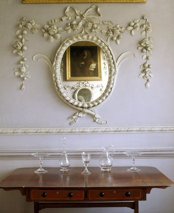 A detailed close up of an oval mirror, table and collection of glassware
