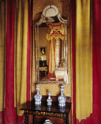 A close up of a mirror and curtains in the Queen Anne Room