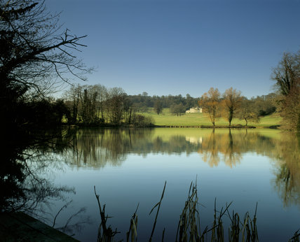 A view across the lake in Dinton Park to Philipps House, an early C19th neo grecian house, in the distance