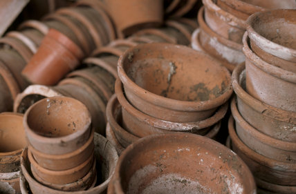 Close view of terracotta flower pots stacked in piles in the shed at Westbury Court Garden, Gloucestershire