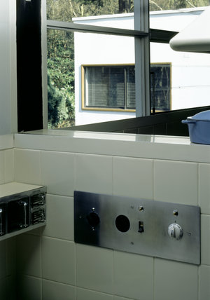 Partial view of a tiled corner of the Kitchen at The Homewood showing the stainless steel electrical panel and the metal and glass unit holding containers for seeds and culinary materials