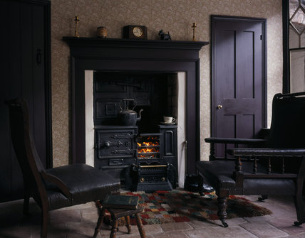 The fireside in the living room of the 1930s house showing the range, mantlepiece, and two easy leather armchairs, in one of the Birmingham Back to Backs