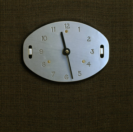 Detail of a metal wall clock in the Living Room at The Homewood, where it is mounted on a wall that has textured covering
