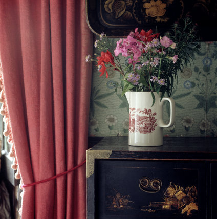 Jug with flowers on an Oriental Cabinet C18th next to the red curtains in the bedroom at Hill Top, the home of Beatrix Potter in Sawrey, Cumbria