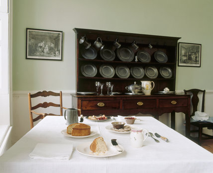 The Common Parlour with the table laid with tea and cakes and the dresser behind, at Wordsworth House
