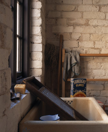 The Wash House which opens onto the communal courtyard of the Birmingham Back to Backs showing the butler's sink, washboard, soap, enamel jug, mop, clothes horse & a Sunlight Flakes packet