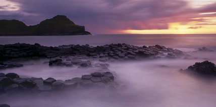 View of the Giant's Causeway in Northern Ireland at sunset with the polygonal columns of layered basalt going into the sea and a headland in the distance