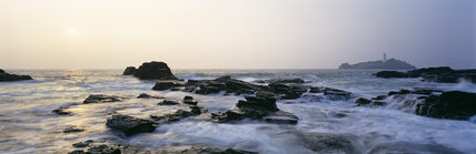 The sea breaks on the scattered rocks with the Godrevy Lighthouse in the distance behind