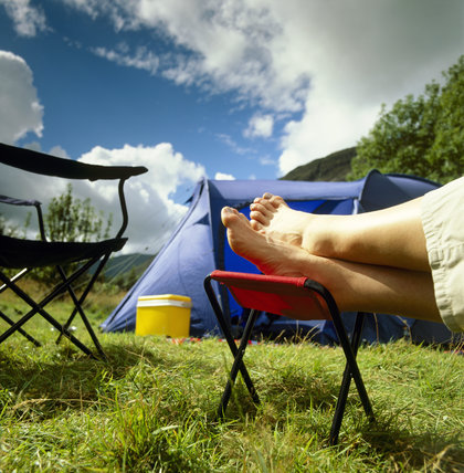 Close shot of a visitor's feet resting on a campstool near a tent on the campsite at Wasdale