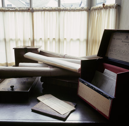 View of a room in the W.M.Heelis Offices, now the Beatrix Potter Gallery at Sawrey showing a table with a filing box and rolled up papers.