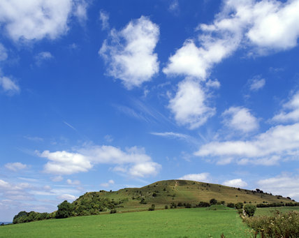 A view of Cley Hill, Wiltshire, standing out against the blue sky, across which cottonwool clouds are scudding