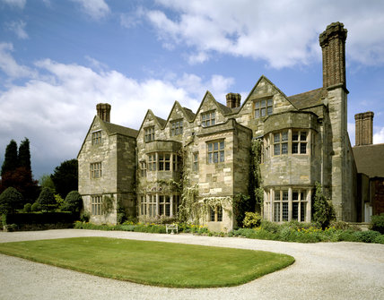 The garden front of Benthall Hall, a 16th century stone house, with a grassy forecourt