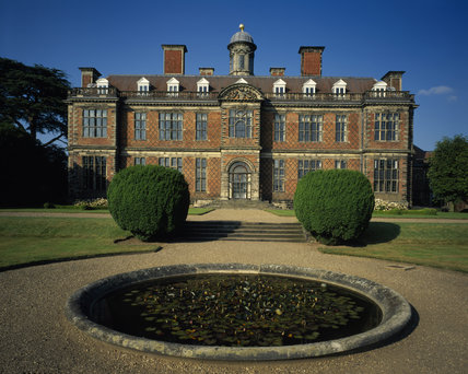 The south front of Sudbury Hall standing out against the blue sky, with the lily pond in the foreground
