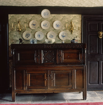 (FL) A local carved oak press cupboard at Hill Top, bought by Beatrix at a local farm sale, above which hang eight plates painted with animals and birds by her father, Rupert