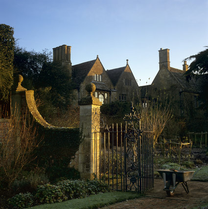 A wheelbarrow on a red brick path beside an iron gateway with the House at Hidcote in the background