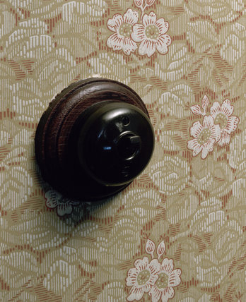 Detail of a bakelite light switch mounted on a wooden surround in the 1930s Living Room of the Birmingham Back to Backs