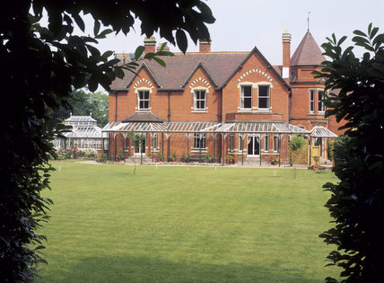 A view across the lawn to the rear of Sunnycroft, a fine late- Victorian gentleman's suburban villa, with verandah, wooden seats and large flowerpots containing flowering shrubs