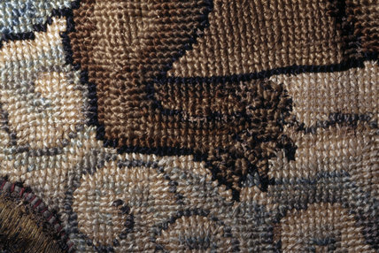 The back legs and part of the hind quarters of a creature from a motif on the Marian Needlework at Oxburgh Hall