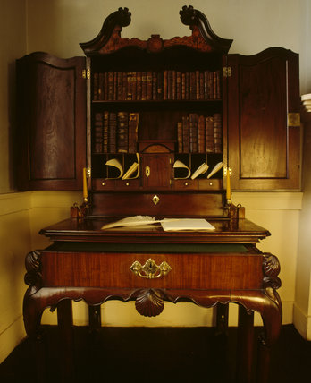Irish 18th century mahogany writing desk at Florence Court, rococo with curved broken pediment, shell decoration, scalloped edge to lower drawer with pigeon holes and books above