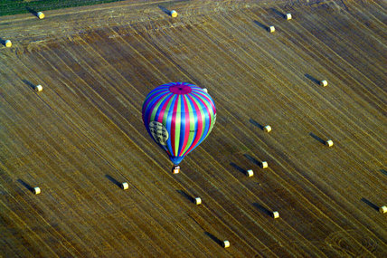 A hot air balloon from the Blickling Balloon Festival flying over agricultural farmland in East Anglia near Blickling Hall