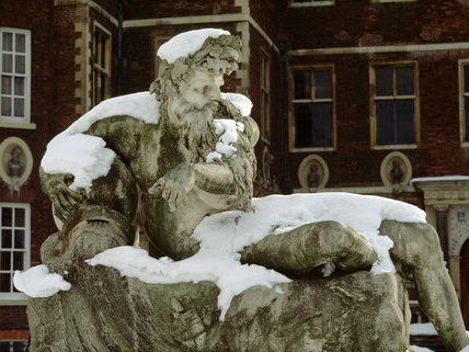 View of the Coade stone river god covered in snow, on the North Forecourt of Ham House