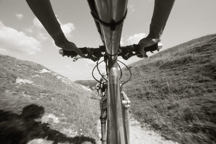 A close-up of a cyclist on his mountain bike at Fulking Escarpment, Devil's Dyke Estate
