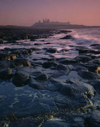 Dramatic view across rocks and sea to Dunstanburgh Castle set against the sunrise